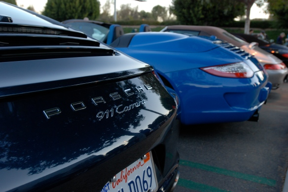 Dark Blue metallic 2013 Porsche type 991, 911 Carrera_ partial rear view with sunrise reflections and 997 Speedster in background_Cars&Coffee/Irvine_January 12, 2013