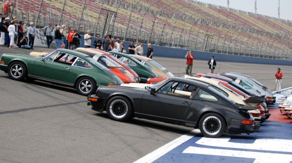50th anniversary  of the Porsche 911 display_911s ( first two rows) aligned on banked track for group photo_California Festival of Speed_April 6, 2013