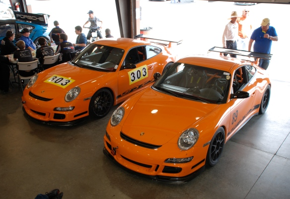 A pair of orange 2007 Porsche GT3RS_#303,#389_ 3/4 front view_Garage 3_California Festival of Speed_April 6, 2013