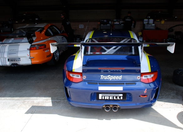 White, blue and yellow striped Justice Brothers Porsche GT3 cup car #94_garage 2_rear view_California Festival of Speed_April 6, 2013