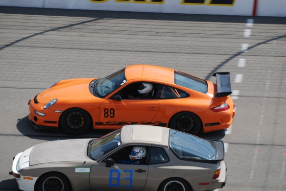 Orange 2007 Porsche GT3 RS #89 and silver Porsche 944 # 83 at speed_California Festival of Speed_April 6, 2013