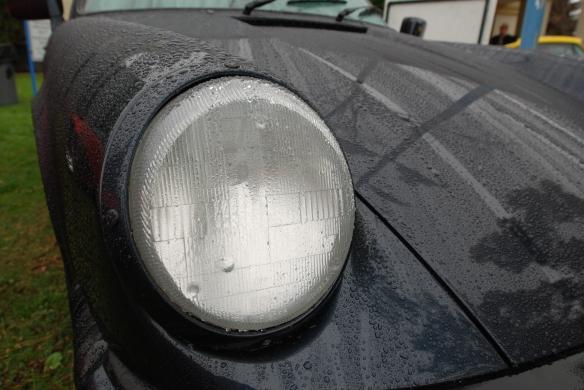 Dark blue Porsche 911 Carrera_headlight, fender and hood shot with raindrops_Phoenix Club Car show & Swap_March 3, 2014