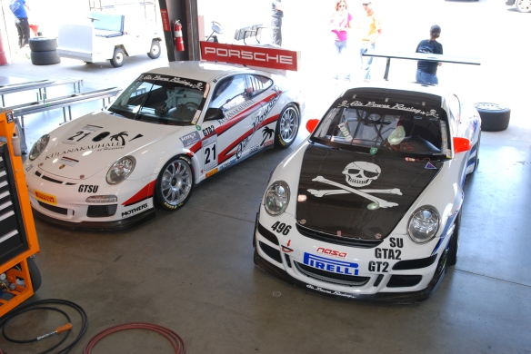 Pair of white Air powered racing  type 997 GT3 Cup car_ 3/4 front view in garage _California Festival of Speed_4/5/14