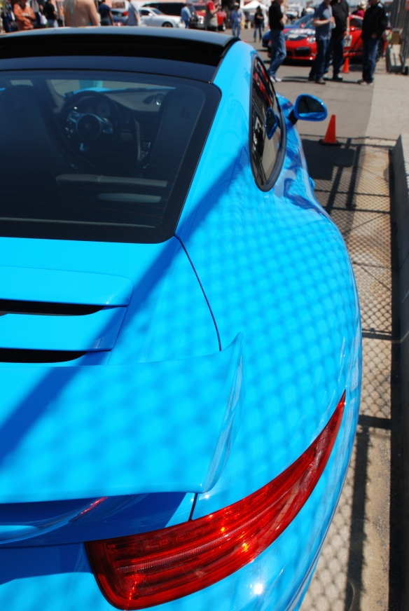 2013 Riviera Blue Porsche 991 w/ aerokit_3/4 rear view with fence shadows on pit row_California Festival of Speed_4/5/14